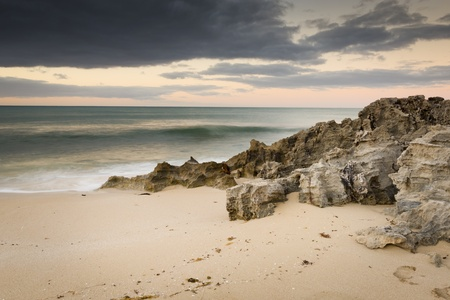 Storm clouds creep in over the ocean with rocks and sand photo