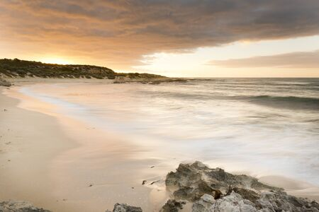 yorke: Spectacular sunset over a beach with smooth time-lapse water and sand