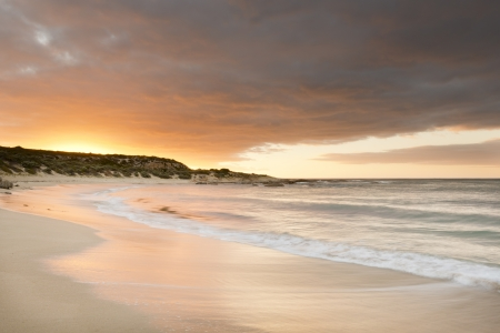 Spectacular sunset over a beach with smooth time-lapse water and sand photo