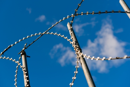 Razor wire on a perimeter fence against a blue sky photo