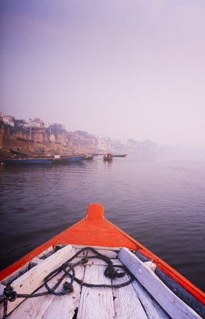 ganges: Rowing a wooden boat down the Ganges River, India at sunrise