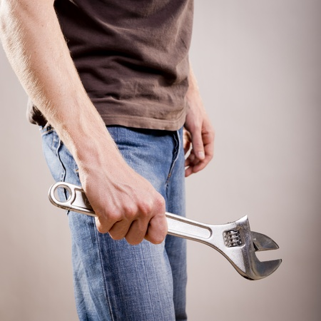 A young man dressed in casual clothes holds a large adjustable wrench or spanner photo