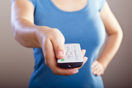 out of control: Woman holds a remote control in her hands with her body out of focus