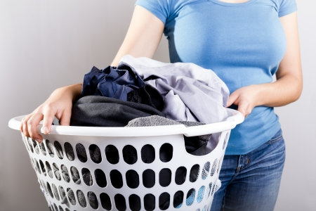 laundry pile: Casually dressed woman in blue shirt holding a basket full of dirty laundry needing washing