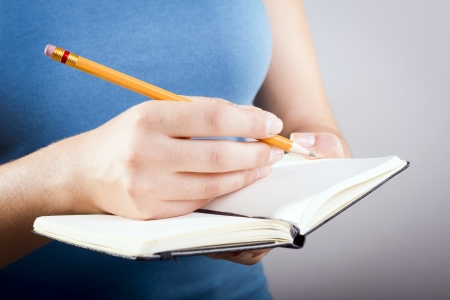 Casually dressed woman in blue shirt writing with a pencil in a small black notebook photo