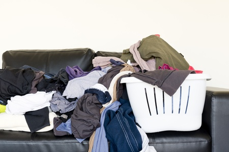 put away: Housework concept of a large pile of laundry dumped on the couch, waiting to be folded and put away