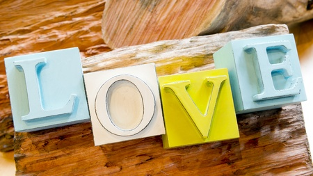 The word Love spelled out in big block letters on a rustic wooden background photo