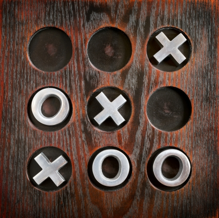 tic tac toe: Game of Tic Tac Toe or Noughts and Crosses on a wooden board with metal pieces