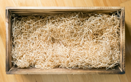 Wooden gift or display box filled with natural raffia or twine Stock Photo