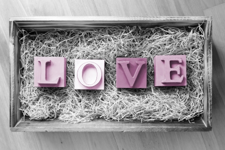 The word Love spelled out in big block letters in a wooden gift box filled with raffia photo