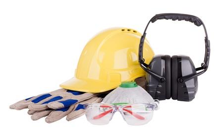 Veiligheidsuitrusting of PBM - persoonlijke beschermingsmiddelen - met hard hat, veiligheidsbril, handschoenen, gezichtsmasker en oorbeschermers op wit wordt geïsoleerd Stockfoto