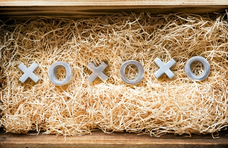 xoxo: Hugs and kisses symbols xoxo in a wooden gift box filled with natural raffia Stock Photo