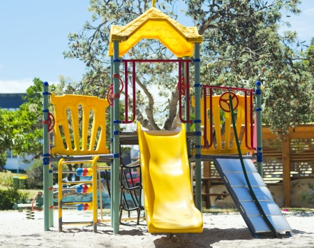 Playground equipment including a yellow slide in a park photo