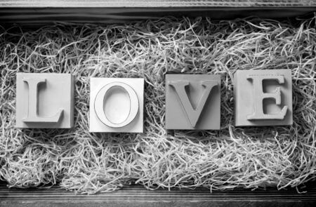 The word Love spelled out in big block letters in a wooden gift box filled with raffia in stunning black and white photo