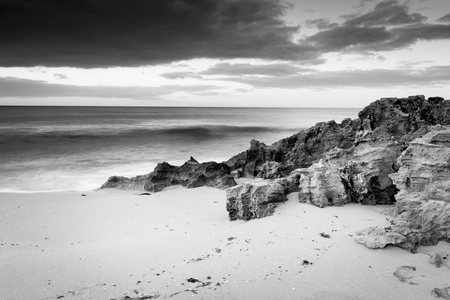 Storm clouds creep in over the ocean with rocks and sand in stunning black and white photo