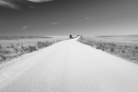 country roads: Dirt road in country Australia stretches into the distance under a blue sky in stunning black and white