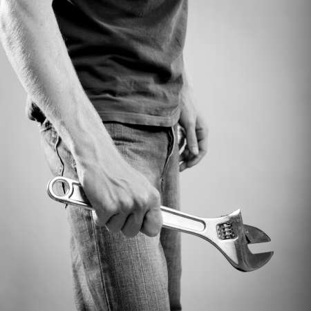 A young man dressed in casual clothes holds a large adjustable wrench or spanner in stunning black and white
