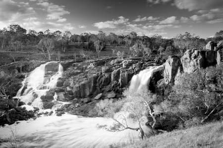 timelapse: Beautiful Nigretta Falls waterfall in Western Victoria, Australia with high flow during winter time in time-lapse in stunning black and white
