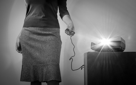 35mm: Retro styled woman operating a slide projector with a wired remote control and lens flare from projector light in stunning black and white Stock Photo