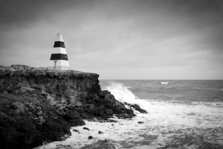 Beacon on a cliff top with waves crashing underneath a stormy sky in stunning black and white photo