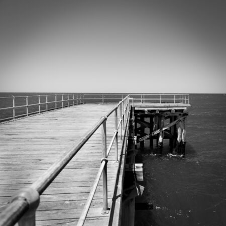 Long wooden jetty stretches out into clear water at Stenhouse Bay, South Australia in stunning black and white photo