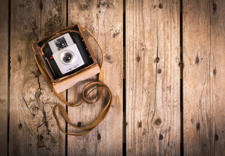 An old camera in its original vintage leather case on a wooden photo