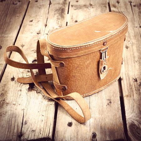 satchel: Old vintage leather bag with leather strap on wooden table filtered Stock Photo