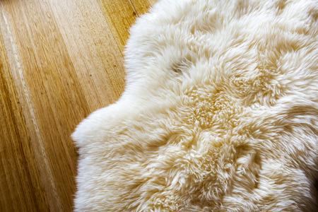 sheepskin: Corderos de piel de oveja de lana en un piso de madera Foto de archivo