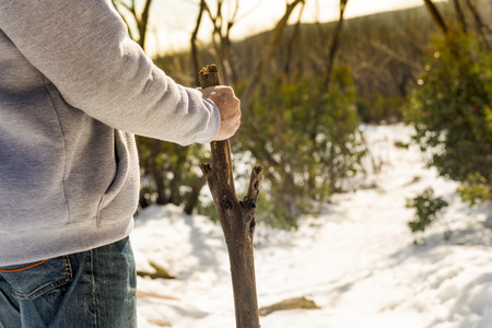 guy with walking stick: An senior aged retired man walking in the snowy mountain Stock Photo