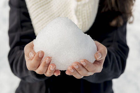 A woman holds a huge snowball in bare hands in shallow focus photo