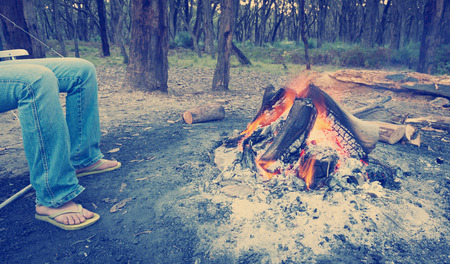 woodfire: Person warms their feet next to a campfire at dusk camping in the woods     Stock Photo