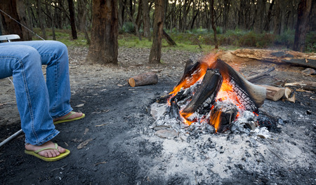 woodfire: Person warms their feet next to a campfire at dusk camping in the woods