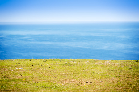 grassy knoll: Green field with ocean behind and blue sky with shallow focus on the grass only