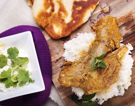 jus: Slow cooked lamb shanks served on wooden board with rice and gluten free naan bread