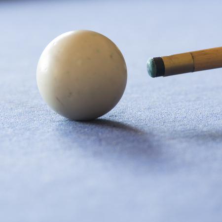 snooker halls: Pool cue and the white ball in shallow focus on a pool table Stock Photo
