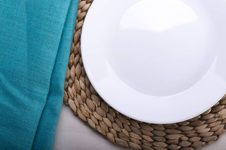 plates of food: Round clean empty white plate on wooden mat