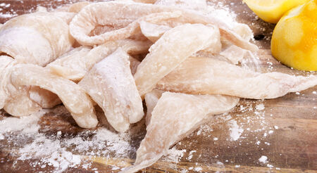 flathead: Fresh flathead fish fillets coated in flour ready for cooking with lemons Stock Photo