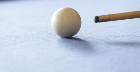 billiards hall: Pool cue and the white ball in shallow focus on a pool table Stock Photo