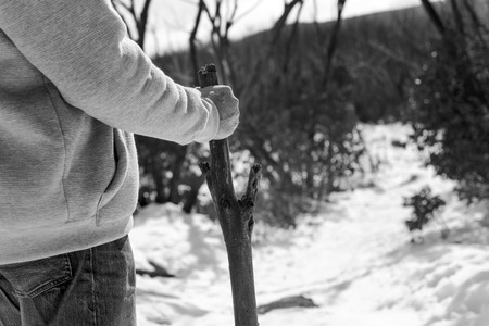 An senior aged retired man walking in the mountains for exercise with a walking stick in black and white photo