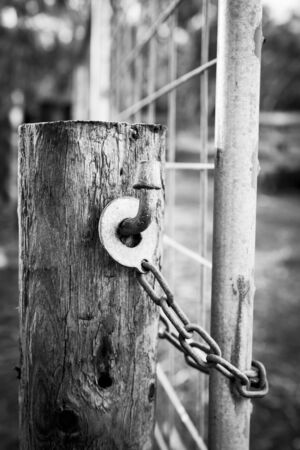 land locked: Classic Australian farm gate lock on a wooden post in black and white Stock Photo