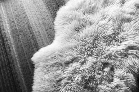 Lambs wool sheepskin on a timber floor in black and white