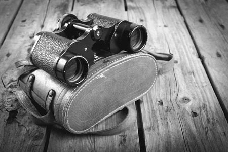 Pair of old binoculars with vintage leather strap and case on a rough wooden surface filtered in black and white photo