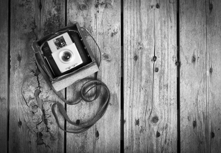 black and white frame: An old camera in its original vintage leather case on a wooden in black and white Stock Photo