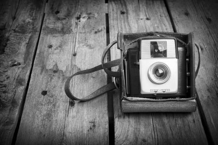 grayscale: An old camera in its original vintage leather case on a wooden in black and white Stock Photo