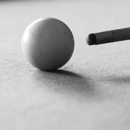 pool cue: Pool cue and the white ball in shallow focus on a pool table in black and white