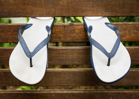 thongs: Flip flops or thongs hanging from a wooden wall at a beach resort