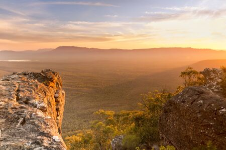 valley below: Mountain top views looking out over valley plain below in sunset light Stock Photo