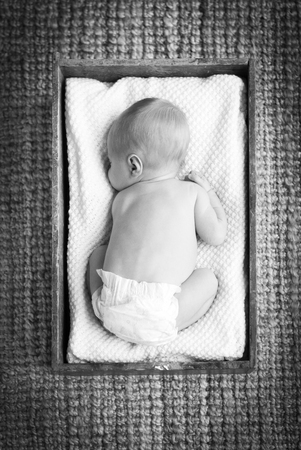 new baby: Newborn baby sleeping in a vintage wooden crate with white cloth in beautiful black and white