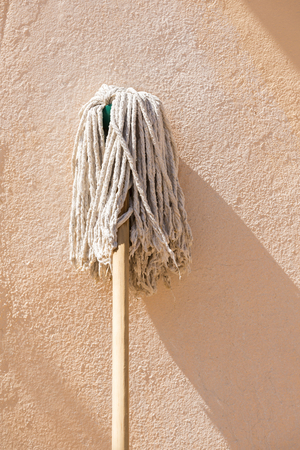 handled: Classic wooden handled mop leaning up against a wall with room for text Stock Photo