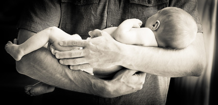 bare chest: Cute newborn baby boy being held in his fathers arms against a bare chest